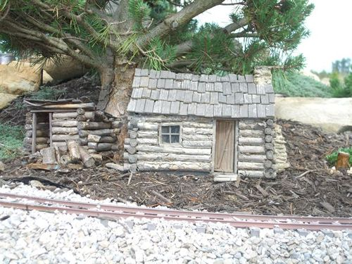 A small Log Cabin under a miniature live Pine tree.